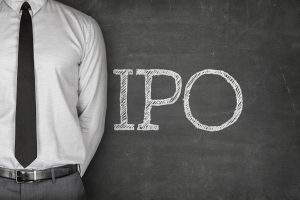 IPO or Initial public offering text on blackboard with businessman on side